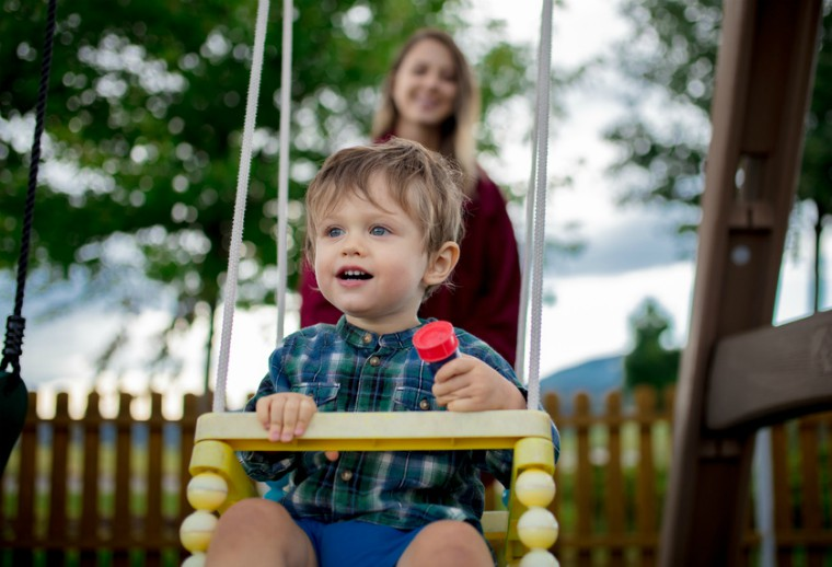 Toddler on swing with mum