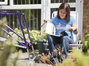 young woman who uses walking frame studying in garden