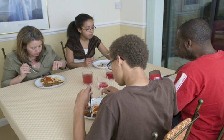 adults and young people eating dinner in residential home residential care