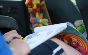 child in car seat colouring in