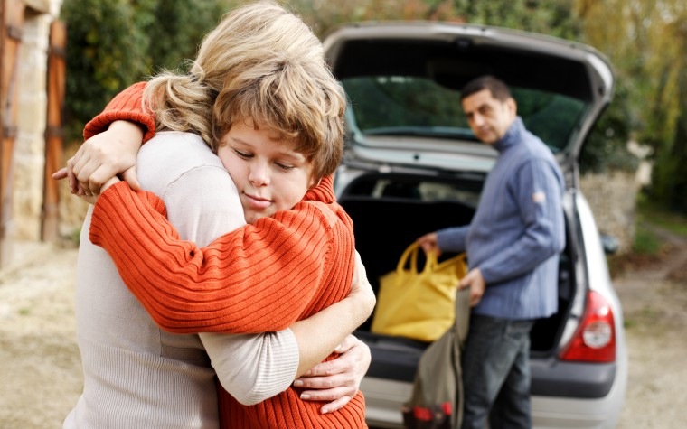 12 year old boy hugging woman car in background