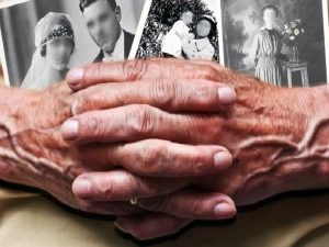 description_of_image_used_in_putting_dementia_policy_objectives_into_practice_two_hands_holding_photos_gabriele_rohde_fotolia