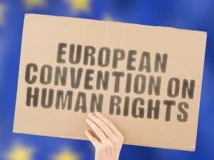 "The phrase ""European Convention on Human Rights "" on a banner in men's hand with blurred European Union flag on the background."