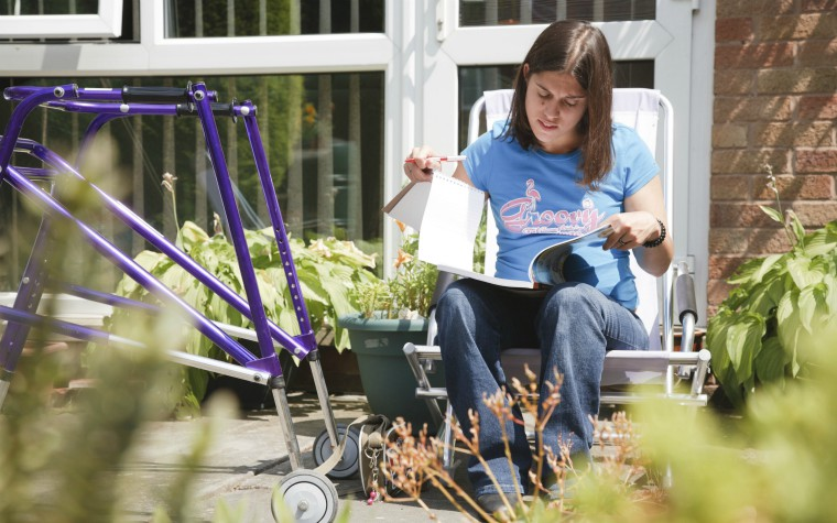 young woman with cerebal palsy studying in garden