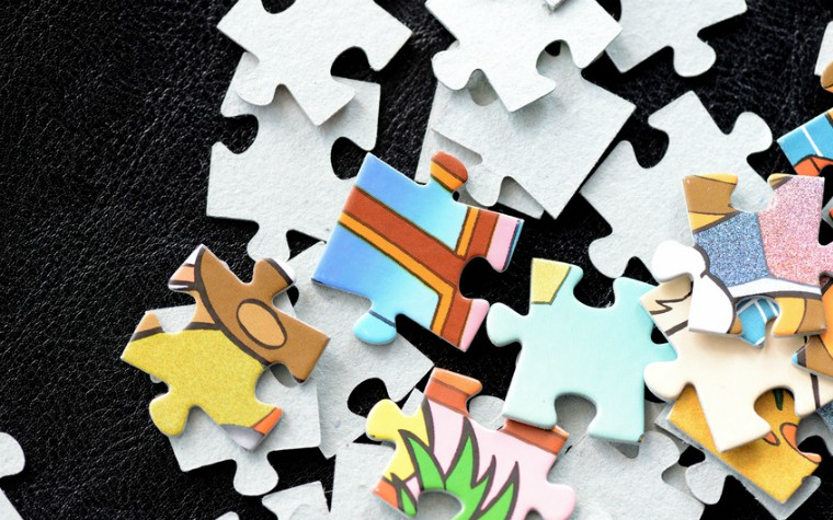 Children's puzzles scattered on a dark surface close-up
