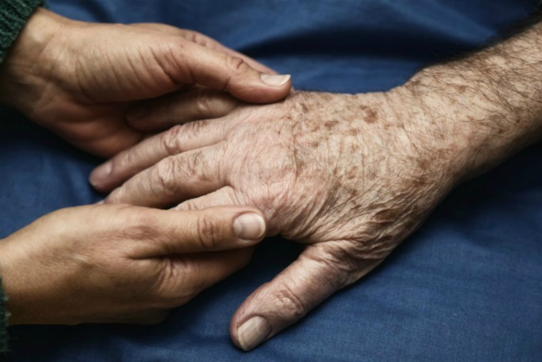 Person holding hand of older person