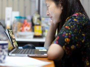 Woman watching group call on laptop screen, wearing a dark floral dress and dark hair