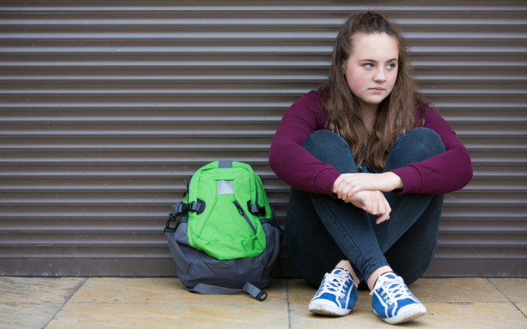 teenage girl sitting on side of street