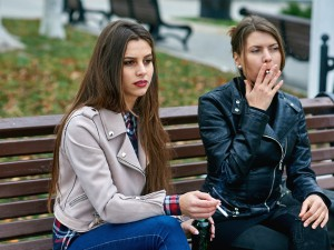 girls smoking on park bench