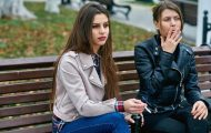 teenage girls smoking on bench