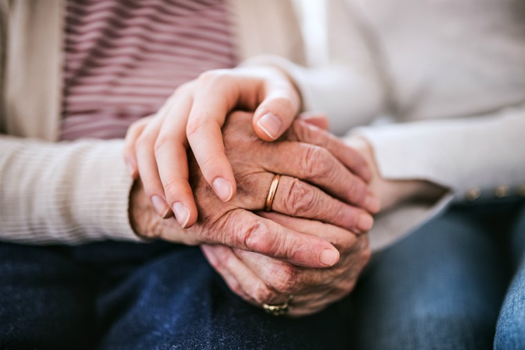 Old woman's hands being held by younger woman's hands