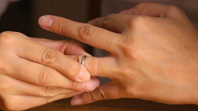 Person taking off wedding ring