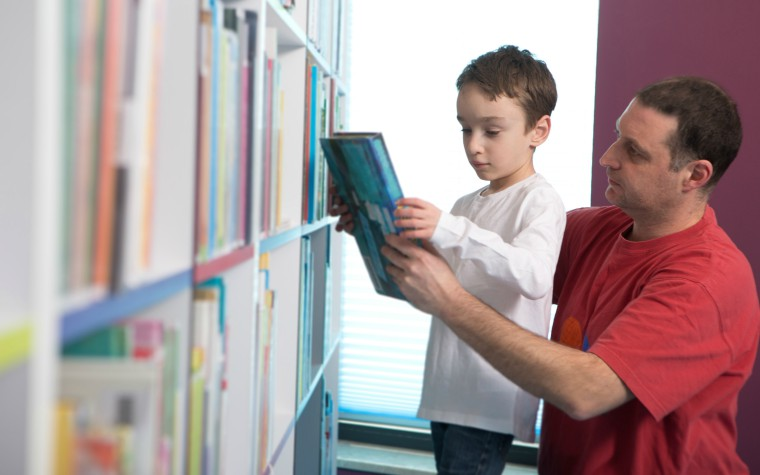 father and son choosing books in a contact centre