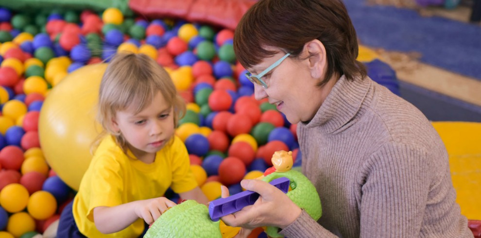 child and adult interacting with toys at a play centre