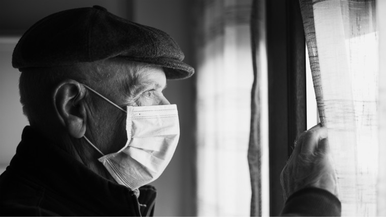 Older man with mask for coronavirus looking out of window