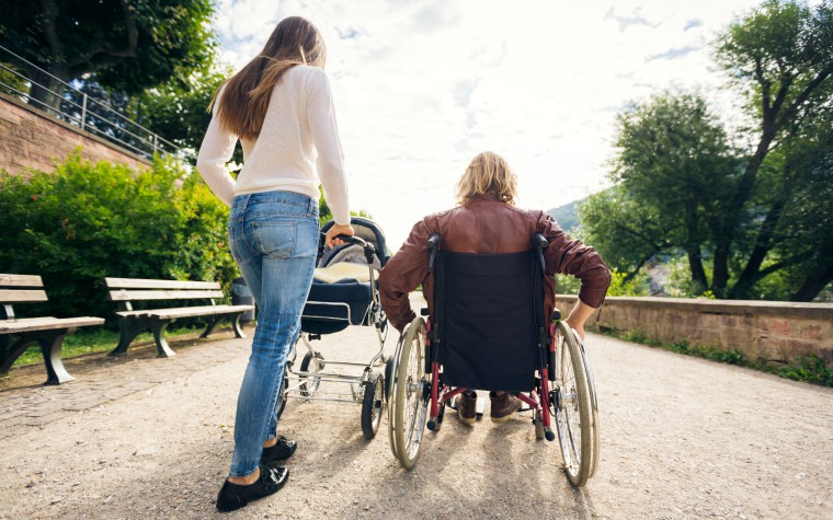 Young carer - pushes pram with parent in wheelchair