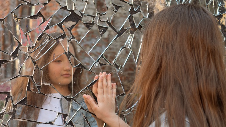Girl puts her hand to reflection in broken mirror - multiple reflections and identities