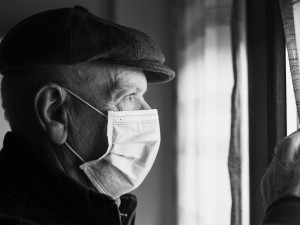 Older man wearing mask looking out of a window