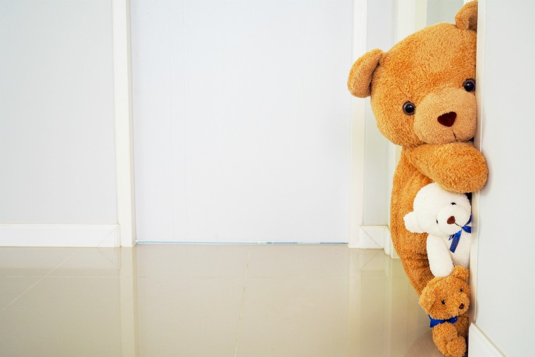 teddy bears peering out from behind a door