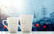 Two coffee cups with smiley face and sad face