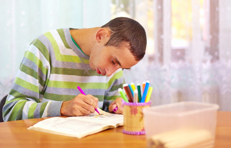 Young man with learning disabilities writing
