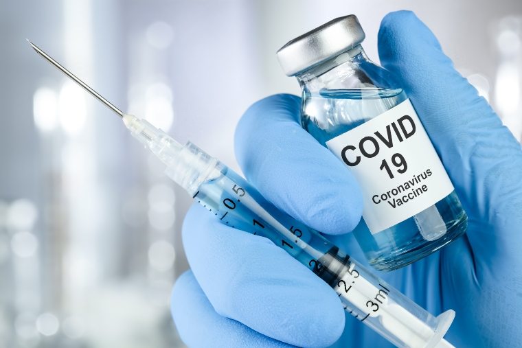 Hand in blue medical glove holding the Covid-19 vaccine in a bottle with needle
