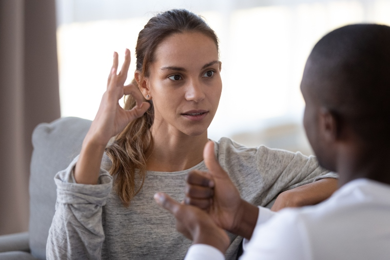 woman using sign language to communicate with a man