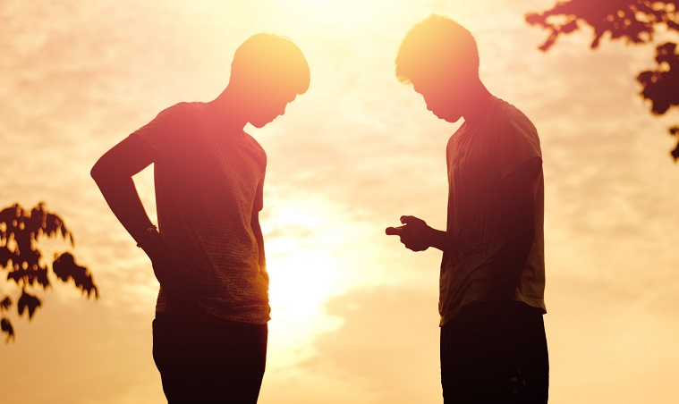 The silhouette of two young men