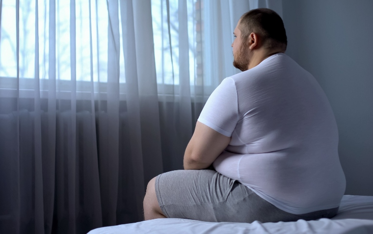 Overweight man sitting on bed with back to camera