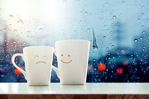 two coffee cups with faces. One offering encouragement to the other