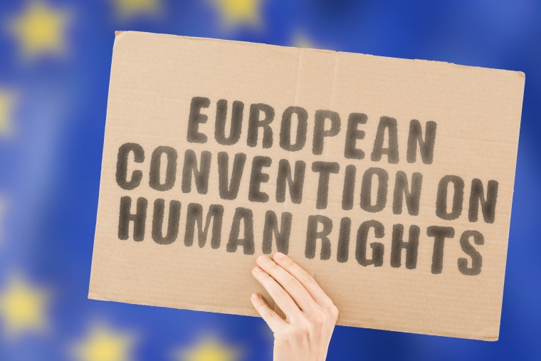 """The phrase """"European Convention on Human Rights """" on a banner in men's hand with blurred European Union flag on the background."""