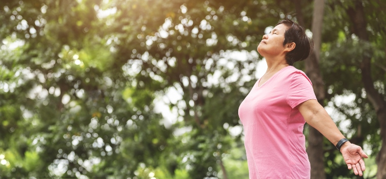 Woman taking a deep breath with arms wide open and eyes shut outside