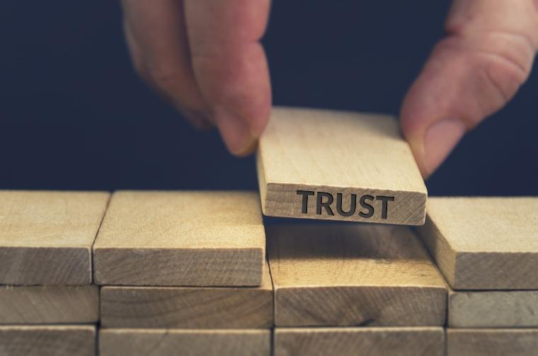 Trust word written on wooden block