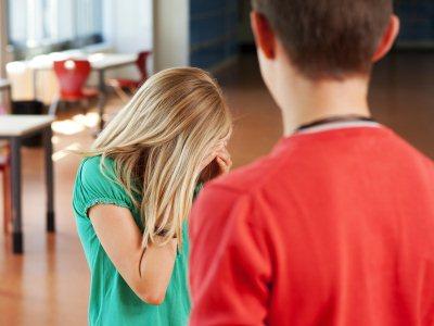 Sad teenage girl standing with teenage boy