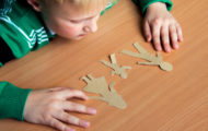 description_of_image_used_in_family_group_conferences_guide_child_looking_at_cut_out_paper_figures_of_family