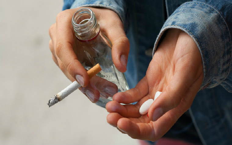description_of_image_used_in_street_drugs_categories_and_effects_man_carrying_pills_cigarette_and_bottle_photographee_fotolia