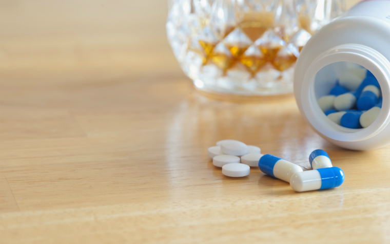 Description_of_image_used_in_alcohol_drugs_research_review_whiskey_and_pills_on_table_rex_shutterstock