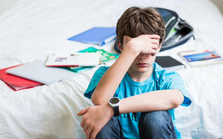 description_of_image_used_in_dealing_with_disruption_older_boy_sitting_alone_in_bedroom_with_his_face_in_his_arms_isopix_rex_shutterstock
