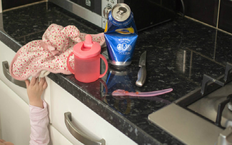 Description_of_image_used_in_neglect_home_visits_quick_guide_child_playing_with_dangerous_objects_in_kitchen