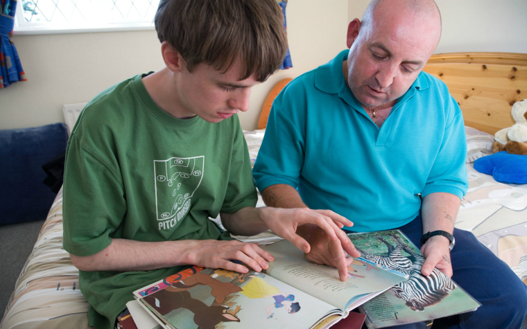 Description_of_image_used_in_autism_act_legislation_teenage_boy_with_autism_reading_with_carer_John_Birdsall_REX_Shutterstock