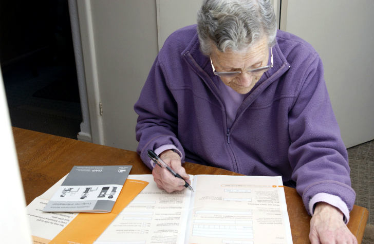 Description_of_image_used_in_disabled_persons_legislation_older_woman_filling_out_assessment_form_EMWelch_REX_Shutterstock