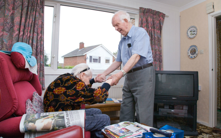 description_of_image_used_in_older_carers_research_review_elderly_man_helping_disabled_wife_out_of_chair_johnbirdsall_rex_shutterstock