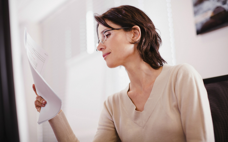 description_of-image_used_in_quality_assuring_guide_woman_reading_sheet_of_paper