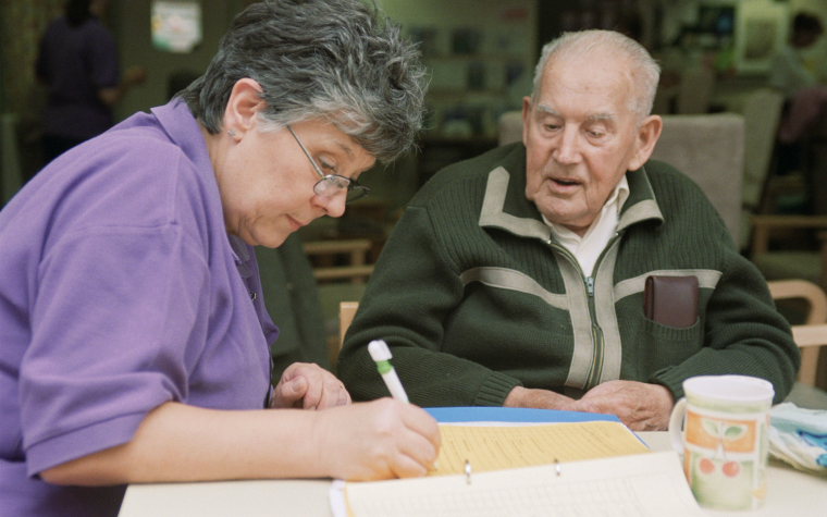 description_of_image_used_in_care_act_eligibility_webinar_learning_tool_social_worker_assessing_older_man_johnbirdsall_rex_shutterstock