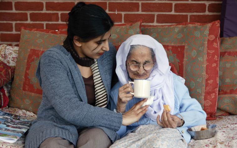 description_of_image_used_in_dementia_knowledge_practice_hub_older_bme_woman_drinking_tea_in_bed_johnbirdsall_rex_shutterstock
