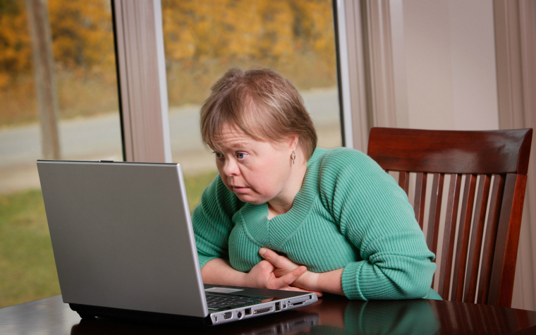 description_of_image_used_in_disability_knowedleg_practice_hub_woman_with_downs_syndome_working_on_laptop_designpicsinc_rex_shutterstock