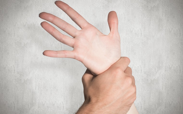 One person's hand gripping another person's wrist