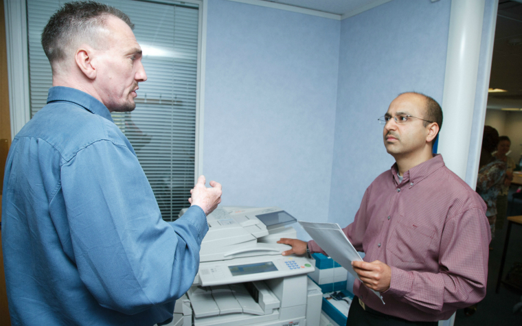 description_of_image_used_in_CPEL_and_professional_judgment_learning_tool_two_work_colleagues_talking_by_printer