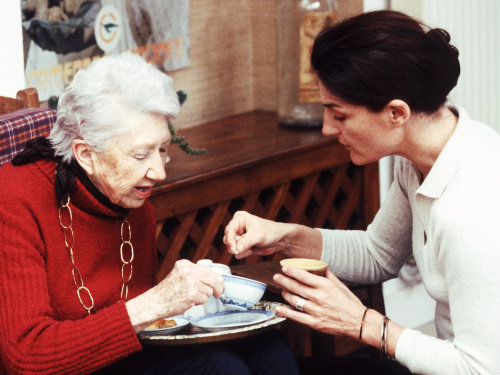 Care worker helping an elderly woman with her medication