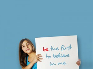 """Woman holding placard saying """"be the first to believe in me"""""""